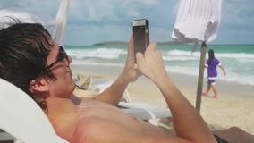 Young man using smartphone while lying on sunbed on tropical beach with turquoise sea background. 3840x2160. Young man using smartphone while lying on sunbed by stock video