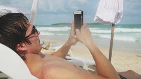 Young man using smartphone while lying on sunbed on tropical beach with turquoise sea background. Stock Photo