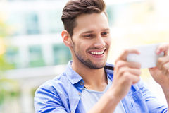 Young man using smartphone Royalty Free Stock Photography