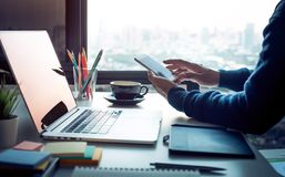 Young man using smartphone with modern work table and computer laptop and cityscapes view from window.Business concepts ideas. stock photography