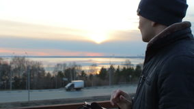 Young man using smartphone outdoor standing on roof bridge. Sunset cityscape stock video footage