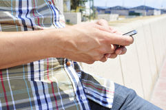 Young man using a smartphone outdoors Royalty Free Stock Photography