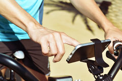 Young man using a smartphone riding a bicycle Stock Photo