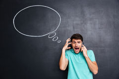 Young man using smartphone and shouting with empty speech bubble Royalty Free Stock Photography
