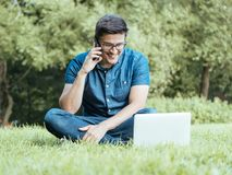 Young man using smartphone while sitting on grass Royalty Free Stock Photography
