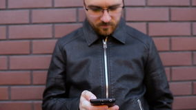 Young man using smartphone standing by brick wall in city stock video footage