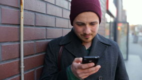 Young man using smartphone standing by brick wall in city stock footage