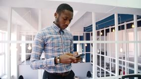 Young man is using smartphone, standing in modern office. African person looks attentively at gadget screen, touching it with fingers, communicating with stock video footage