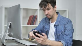 Young Man Using Smartphone while Working on Desktop. The Young Man Using Smartphone while Working on Desktop, high quality stock video
