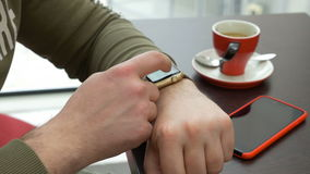 Young man using smartwatch email app while sitting at a coffee shop. Young man using smartwatch email app while sitting at coffee shop stock video footage