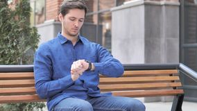 Young Man Using Smartwatch, Outdoor Sitting on bench. 4k high quality, 4k high quality stock footage