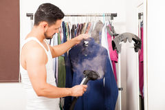 Young man using a steamer on his clothes. Profile view of a good looking young man using a steamer on a shirt before getting dressed Stock Photos