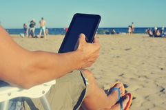 Young man using a tablet on the beach Stock Photos