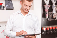 Young man using tablet at boutique Stock Images