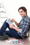 Young man using tablet while choosing color of his flat Stock Photo
