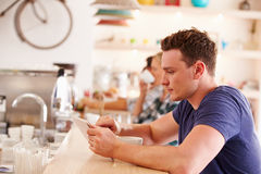 Young man using tablet computer in a cafe Royalty Free Stock Photo