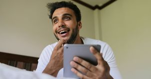 Young Man Using Tablet Computer Lying On Bed Pondering Smiling Hispanic Guy Chatting Online In Bedroom Morning stock footage