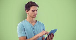 Young man using tablet computer over green background. Digital composite of Young man using tablet computer over green background Royalty Free Stock Photo