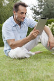 Young man using tablet computer in park Royalty Free Stock Photos