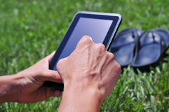 Young man using a tablet computer in a park Royalty Free Stock Photo
