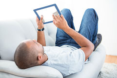 Young man using tablet computer on sofa Royalty Free Stock Photography