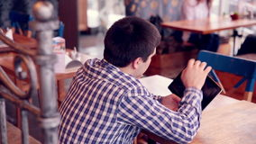 Young man using tablet computer touchscreen in cafe. HD stock video footage
