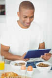 Young man using tablet and eating breakfast in kitchen Stock Photo