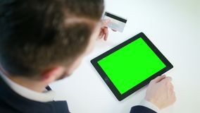 A Young Man Using a Tablet with a Green Screen. And holding a credit card indoors.View from the top. Close-up shot. Soft focus stock video