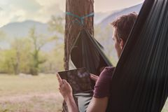 Young man using a tablet on a hammock stock photography