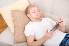 Young man using a tablet at home Royalty Free Stock Image