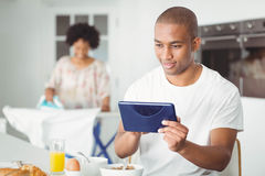 Young man using tablet in kitchen Stock Photo