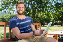Young man using tablet on park bench Royalty Free Stock Photography
