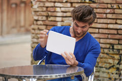 Young man using tablet pc as a mirror fixing hair Stock Photography