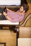 Young man using a tablet pc in a asian hotel room Royalty Free Stock Photo