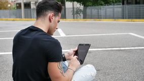 Young man using tablet PC outdoor in city. Young attractive man using tablet PC outdoor in city setting, in summer day stock video