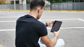 Young man using tablet PC outdoor in city Royalty Free Stock Image