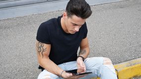 Young man using tablet PC outdoor in city Stock Images
