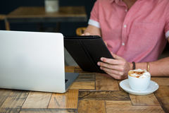 Young man using tablet PC at table in coffee shop Stock Photography
