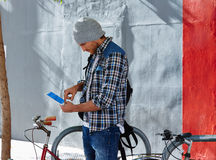Young man using tablet pc touch in a bicycle Royalty Free Stock Photography