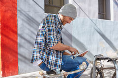 Young man using tablet pc touch in a bicycle Stock Images