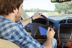 Young man using tablet while sitting in the car. Young man using his digital tablet while sitting in the car Stock Photos