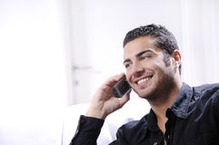 Young man using telephone. Smiling and calling on white background Royalty Free Stock Image