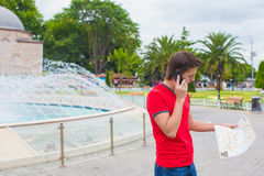 Young man using telephone with map in hands Stock Photography