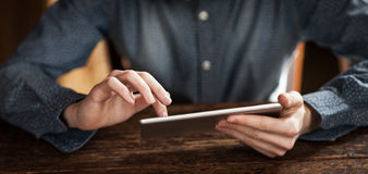 Young man using a touch screen tablet Stock Photography