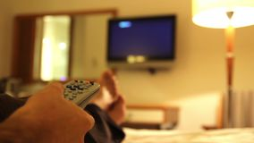 Young man watching tv in hotels room. Young man using tv in hotels room, feet in hotel stock footage
