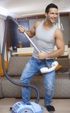 Young man using vacuum cleaner as guitar Royalty Free Stock Photography