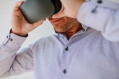 Young man using Virtual Reality glasses. Closeup shot of young man using Virtual Reality glasses. Businessman wearing VR goggles Royalty Free Stock Image