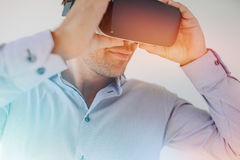 Young man using VR glasses. Closeup shot of businessman wearing virtual reality goggles against grey background. Young man using VR glasses with sun flare effect Royalty Free Stock Photos