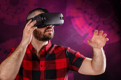 Young man using VR glasses. Headset trying to touch objects in virtual reality Royalty Free Stock Photo