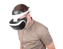 Young man using a VR headset and experiencing virtual reality isolated on a white background. An adult boy in virtual reality. royalty free stock photography